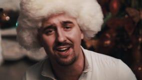 Αοιδός Unshaved στη συνεδρίαση τραγουδιού καπέλων γουνών στο δωμάτιο με τις διακοσμήσεις Χριστουγέννων απόθεμα βίντεο