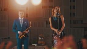 Αοιδός της Jazz στο καμμένος φόρεμα στο μικρόφωνο Saxophonist στο μπλε κοστούμι στη σκηνή φιλμ μικρού μήκους