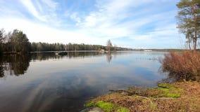 Απίστευτα ειρηνική λίμνη καθαρού νερού που περιβάλλεται από τα δέντρα σημύδων πεύκων και τη φυσική ομορφιά κάτω από το σύννεφο φιλμ μικρού μήκους