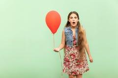 Απίστευτος! Ο όμορφος ξανθός έφηβος είναι sho; ked, εξετάζοντας τη κάμερα, με κόκκινο ballon σε ένα ανοικτό πράσινο υπόβαθρο Στοκ Εικόνες