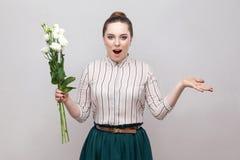 απίστευτος Πορτρέτο της έκπληκτης ρομαντικής νέας γυναίκας στο ριγωτό πουκάμισο και της πράσινης ανθοδέσμης εκμετάλλευσης φουστών στοκ φωτογραφίες