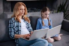 Απαθής μητέρα και λίγη κόρη που κάνουν σερφ το Διαδίκτυο στο εσωτερικό Στοκ Φωτογραφία