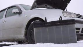 Απαλλαγμένη μπαταρία αυτοκινήτων στο υπόβαθρο του αυτοκινήτου το χειμώνα, η έναρξη προβλήματος στην κρύα εποχή απόθεμα βίντεο