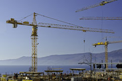 Απασχολημένοι εργαζόμενοι και γερανοί στο εργοτάξιο οικοδομής Στοκ Εικόνες