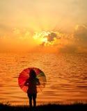 απεικονίστε τη γυναίκα ύδατος ομπρελών ηλιοβασιλέματος σκιαγραφιών Στοκ εικόνες με δικαίωμα ελεύθερης χρήσης