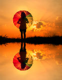 απεικονίστε τη γυναίκα ύδατος ομπρελών ηλιοβασιλέματος σκιαγραφιών Στοκ φωτογραφία με δικαίωμα ελεύθερης χρήσης