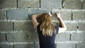 Απελπισμένη δυστυχισμένη γυναίκα από τον τοίχο η έννοια της πίεσης και μάταιος στοκ εικόνες