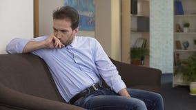 Απελπισμένη συνεδρίαση ατόμων στον καναπέ και σκέψη για την απώλεια χρημάτων, αρνητικές συγκινήσεις απόθεμα βίντεο