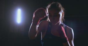 Απεργίες όμορφες θηλυκές μπόξερ άμεσα στη κάμερα που εξετάζει τη κάμερα και που προωθεί σε ένα σκοτάδι φιλμ μικρού μήκους