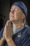 Απελπισμένη γιατρός ή νοσοκόμα θηλυκών που παρακαλεί στην προσευχή Στοκ εικόνες με δικαίωμα ελεύθερης χρήσης