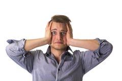 Απελπισμένος, νεαρός άνδρας με τα χέρια στο πρόσωπό του στοκ φωτογραφίες