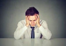 Απελπισμένος λυπημένος νέος επιχειρηματίας που κλίνει σε ένα γραφείο Στοκ φωτογραφίες με δικαίωμα ελεύθερης χρήσης