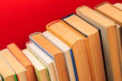 Απλή σύνθεση των βιβλίων βιβλίων με σκληρό εξώφυλλο, ακατέργαστη των βιβλίων στον ξύλινο πίνακα γεφυρών και το κόκκινο υπόβαθρο - στοκ εικόνες
