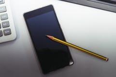 Απλό μαύρο smartphone και κίτρινο μολύβι Στοκ φωτογραφία με δικαίωμα ελεύθερης χρήσης