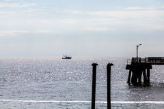 Αποβάθρα πελεκάνων και σκιαγραφία βαρκών γαρίδων στοκ φωτογραφία με δικαίωμα ελεύθερης χρήσης