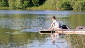 Αποβάθρα ποταμών Παιδιά που καταβρέχουν το νερό στην αποβάθρα απόθεμα βίντεο