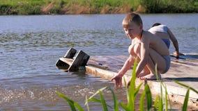 Αποβάθρα ποταμών Παιδιά που καταβρέχουν το νερό στην αποβάθρα φιλμ μικρού μήκους