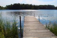 Αποβάθρα που αγνοεί μια λίμνη με τα δέντρα στο υπόβαθρο στοκ φωτογραφία