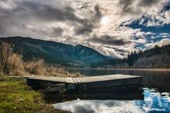 Αποβάθρα στη λίμνη με τα δραματικά σύννεφα Στοκ Εικόνες