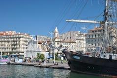 Αποβάθρα στον παλαιό λιμένα της Μασσαλίας με τις σύγχρονες πολυκατοικίες και το με δύο ιστία schooner Marcelinoυ Στοκ Εικόνες