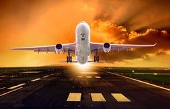Απογείωση επιβατών αεροπλάνου από τους διαδρόμους ενάντια στο όμορφο σκοτεινό SK στοκ εικόνες