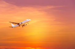 Απογείωση πετάγματος αεροπλάνων επιβατών στο ηλιοβασίλεμα Στοκ Φωτογραφία