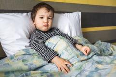 Απογοητευμένη ανεπαρκής συνεδρίαση μικρών παιδιών αγοριών στο κρεβάτι Στοκ φωτογραφία με δικαίωμα ελεύθερης χρήσης