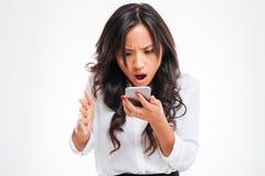 Απογοητευμένη ασιατική επιχειρηματίας που χρησιμοποιεί το smartphone Στοκ Φωτογραφίες