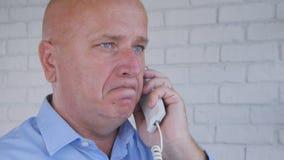 Απογοητευμένη ομιλούσα επιχείρηση επιχειρηματιών που χρησιμοποιεί το τηλέφωνο γραφείων στοκ φωτογραφία