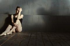 Απογοητευμένη συνεδρίαση χορευτών μπαλέτου στο σκοτεινό αναμμένο δωμάτιο στοκ φωτογραφία με δικαίωμα ελεύθερης χρήσης