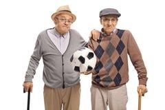 Απογοητευμένοι πρεσβύτεροι που κρατούν ένα ξεφουσκωμένο ποδόσφαιρο Στοκ Φωτογραφίες