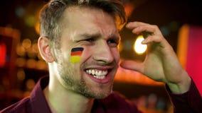 Απογοητευμένος αρσενικός ανεμιστήρας τη γερμανική σημαία που χρωματίζεται με σε ετοιμότητα κυματίζοντας μάγουλων, αποτυχία στοκ φωτογραφία