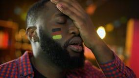 Απογοητευμένος γερμανικός οπαδός ποδοσφαίρου με τη σημαία στο μάγουλο που κάνει facepalm, απώλεια ομάδων απόθεμα βίντεο