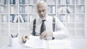 Απογοητευμένος επιχειρηματίας που διαβάζει μια multi-page έκθεση στοκ φωτογραφία με δικαίωμα ελεύθερης χρήσης
