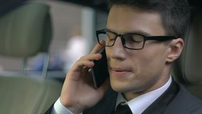 Απογοητευμένος επιχειρηματίας που μιλά στο τηλέφωνο καθμένος στη πίσω θέση του αυτοκινήτου απόθεμα βίντεο