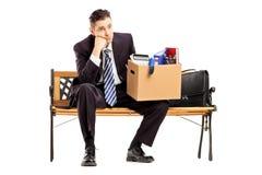 Απογοητευμένος επιχειρηματίας σε μια συνεδρίαση κοστουμιών σε έναν πάγκο με ένα κιβώτιο στοκ εικόνες
