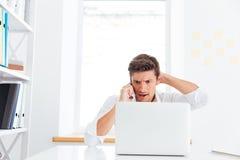 Απογοητευμένος νέος επιχειρηματίας που μιλά στο τηλέφωνο και το κοίταγμα Στοκ φωτογραφίες με δικαίωμα ελεύθερης χρήσης