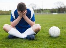 Απογοητευμένος ποδοσφαιριστής στην μπλε συνεδρίαση στην πίσσα μετά από να χάσει Στοκ φωτογραφία με δικαίωμα ελεύθερης χρήσης