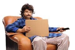 Απογοητευμένος τύπος σε μια πολυθρόνα που κρατά έναν μακρινό και ένα χαρτόνι s Στοκ εικόνες με δικαίωμα ελεύθερης χρήσης