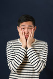 Απογοητευμένο νέο ασιατικό άτομο που καλύπτει το πρόσωπό του από τους φοίνικες Στοκ φωτογραφίες με δικαίωμα ελεύθερης χρήσης