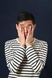 Απογοητευμένο νέο ασιατικό άτομο που καλύπτει το πρόσωπό του από τους φοίνικες Στοκ Εικόνες