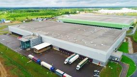 Αποθήκες εμπορευμάτων και φορτηγά στην κεκλιμένη ράμπα ενάντια στην γκρίζα ανώτερη άποψη σύννεφων απόθεμα βίντεο
