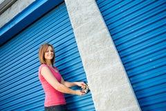 Αποθήκευση: Γυναίκα που βάζει την κλειδαριά στην πόρτα μονάδων Στοκ Εικόνες