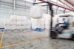 αποθήκευση Forklift οδηγός που συσσωρεύει τη μεγάλη τσάντα της πρώτης ύλης μέσα Στοκ Φωτογραφία