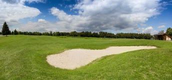 Αποθήκη άμμου στο γήπεδο του γκολφ με την τέλεια πράσινη χλόη στοκ εικόνα