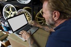 Αποθήκη εμπορευμάτων ιδιοκτητών μαγαζιό μερών αυτοκινήτων που ελέγχει την έννοια lap-top Στοκ φωτογραφίες με δικαίωμα ελεύθερης χρήσης