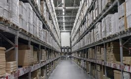 Αποθήκη εμπορευμάτων με τα κιβώτια στα ράφια και τα ράφια στοκ εικόνα με δικαίωμα ελεύθερης χρήσης