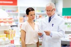 Αποθηκάριος και γυναίκα με τη συνταγή στο φαρμακείο στοκ φωτογραφίες με δικαίωμα ελεύθερης χρήσης