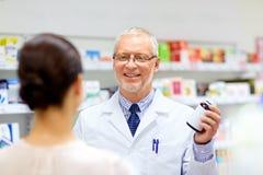 Αποθηκάριος και γυναίκα με το φάρμακο στο φαρμακείο στοκ φωτογραφίες
