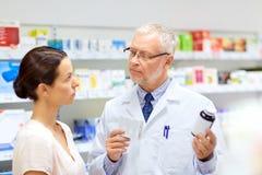 Αποθηκάριος και γυναίκα με το φάρμακο στο φαρμακείο στοκ εικόνα με δικαίωμα ελεύθερης χρήσης